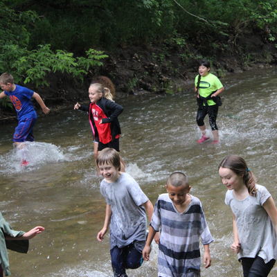 Children explore the creek on school field trips